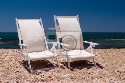 Due sedie bianche su una spiaggia con conchiglia di mare e sabbia
