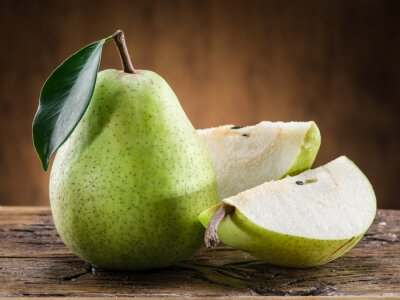 Carta da parati frutta pera con foglia su sfondo di legno.