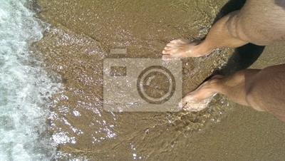 Carta da parati Gambe maschili sulla sabbia costiera bagnata