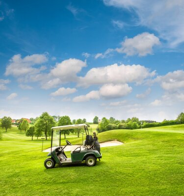 Carta da parati Golf cart su un campo da golf. Campo verde e cielo nuvoloso blu
