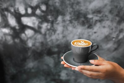 Carta da parati Gray cup of fresh cappuccino in woman hands on background of gray concrete cement textured wall. Trendy hipster cafe design.