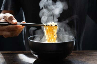 Carta da parati Hand uses chopsticks to pickup tasty noodles with steam and smoke in bowl on wooden background, selective focus. Asian meal on a table, hot food and junk food concept