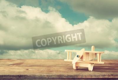 Carta da parati Immagine di legno giocattolo aereo su tavola di legno contro il cielo nuvoloso. Immagine di stile retrò