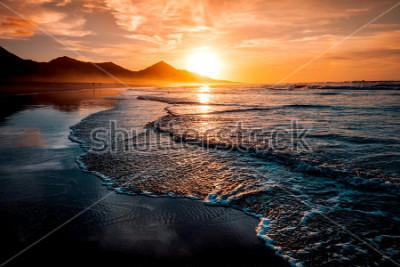 Carta da parati Incredibile tramonto sulla spiaggia con orizzonte infinito e figure solitarie in lontananza e incredibili onde spumeggianti. Colline vulcaniche sullo sfondo in colori caldi idilliaci.