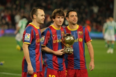 Carta da parati Iniesta, Messi and Xavi of Barcelona with golden ball before a Spanish Cup match between FC Barcelona and Real Betis at the Nou Camp Stadium on January 12, 2011 in Barcelona, Spain