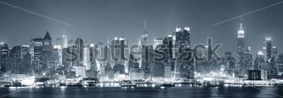 Carta da parati L'orizzonte di Midtown di New York City Manhattan in bianco e nero alla notte con grattacieli si accende sopra il fiume Hudson con le riflessioni.
