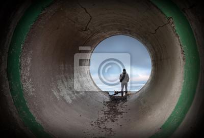 Carta da parati L'uomo guarda l'orizzonte alla fine del tunnel di cemento scuro