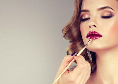 Carta da parati Mano di maestro make-up, la pittura labbra di giovane bellissima modella. Trucco in corso.