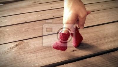Carta da parati Mano in stivali di feltro rosso sta camminando sul tavolo in legno