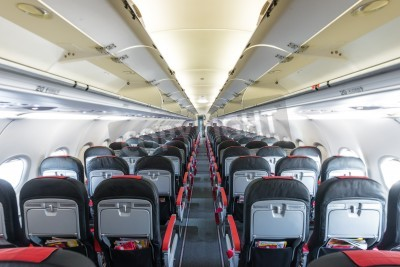 Carta da parati Modern interior of aircraft. Black and red seats inside airplane. Symmetric vanishing row of seats inside air transport. Economy class of flight. Equipment for travelling. Empty illuminated plane.