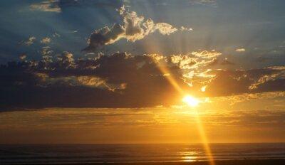 Carta da parati Nuvoloso Tramonto sul mare con raggi di sole nel cielo