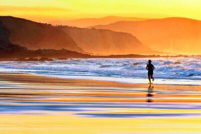 Carta da parati persona in esecuzione sulla spiaggia al tramonto
