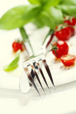 Carta da parati pomodori freschi, coltello e forchetta su un piatto
