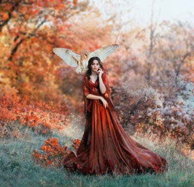 Carta da parati pretty young girl with black hair in cold forest, orange foliage of trees, fairy of autumn season in long red burgundy vintage dress with chic train, lady with white owl on shoulder, bloody sorceress