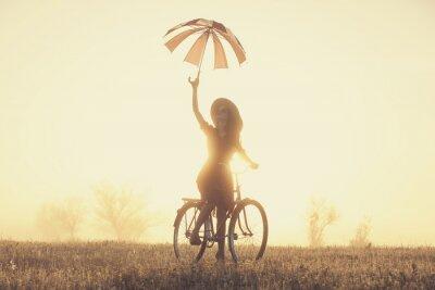 Carta da parati Ragazza con l'ombrello su una bicicletta in campagna in fase di Alba