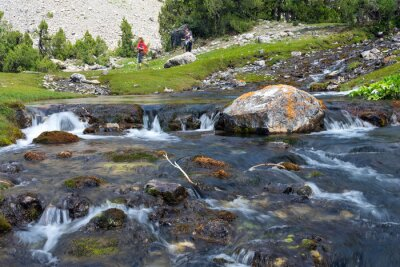 Carta da parati Rapid and wide cascade river Fast moving water vivid rocky stones and group of people walking on green meadow on background