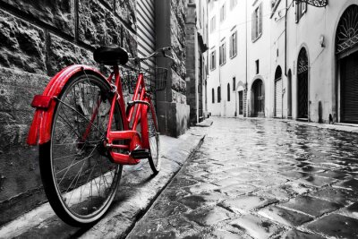 Carta da parati Retro moto rossa d'epoca sulla strada di ciottoli nel centro storico. Colore in bianco e nero