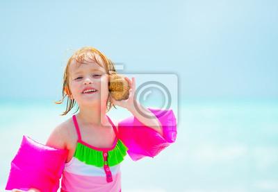 Costume Da Bagno Conchiglia : Ritratto della bambina che ascolta il suono del mare in conchiglia