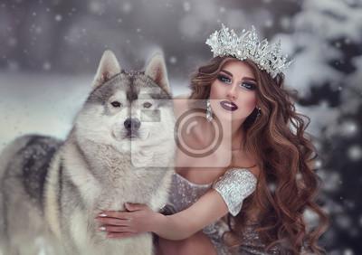Carta da parati Ritratto di donna in abito argento e corona come regina delle nevi, nella foresta invernale con cane Husky. La fata principessa e il lupo in inverno.