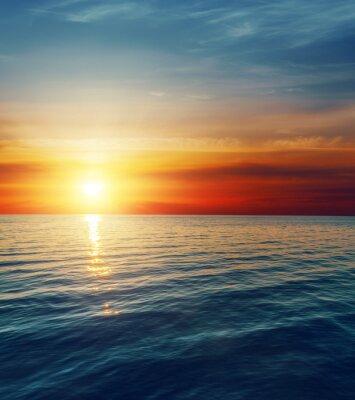 Carta da parati rosso tramonto sopra l'acqua scura