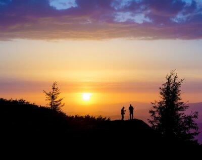 Carta da parati Sagome di due persone in piedi su una roccia vicino all'albero e guardando verso il sole. Tramonto in montagna. Estate nei Carpazi ucraini