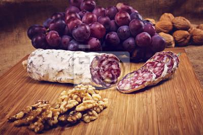 Carta da parati salame con noci su un piatto di legno con l'uva