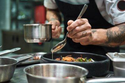 Carta da parati Secret recipe. Close up photo of chef hands with several tattoos adding a sauce to italian pasta Carbonara.