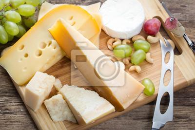 Carta da parati set di vari formaggi con l'uva su sfondo di legno