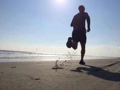 Carta da parati Silhoette di uomo in esecuzione sulla spiaggia