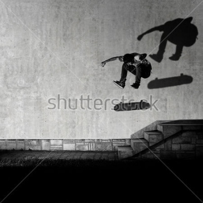 Carta da parati Skater making 360 flip trick from 4 stairs - artistic motion blur shot in black and white color tone.