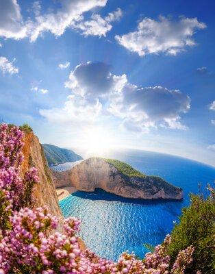 Carta da parati Spiaggia di Navagio con il naufragio e fiori contro tramonto, isola di Zacinto, Grecia