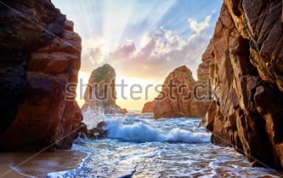 Carta da parati Spiaggia di sabbia tra le rocce sul tramonto della sera. Ursa Beach vicino a Capo Roca (Cabo da Roca) sulla costa dell'Oceano Atlantico in Portogallo. Paesaggio estivo