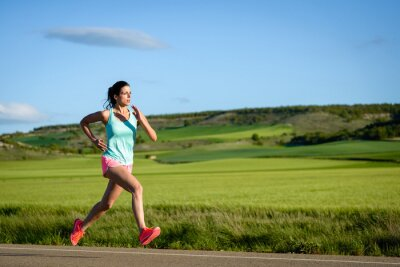 Carta da parati Sporty woman running fast on country side road. Female athlete training outdoor.
