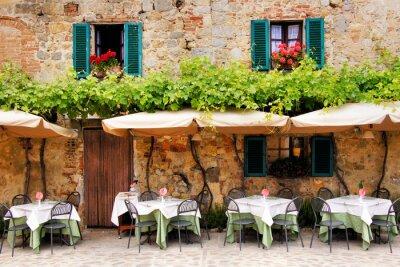 Carta da parati Tavolini del caffè e sedie all'esterno di un edificio in pietra in Toscana