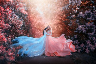 Carta da parati two women in long dresses hugging train flies wind. bright fabulous purple colors art retouching processing. Natural cosmetics scented spring flowers tenderness smell perfume. Blonde brunette hair