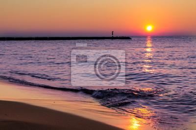 Carta da parati Una calma, serena tramonto in riva al mare e dolci onde che si infrangono sulla spiaggia.