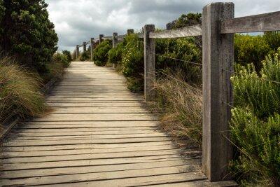 Carta da parati Una passerella in legno lungo una recinzione con vegetazione verde che cresce su entrambi i lati sotto un cielo nuvoloso. Questo si trova da qualche parte lungo la strada grande oceano in Australia.
