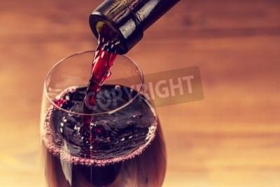 Carta da parati Versare il vino rosso nel vetro su sfondo di legno
