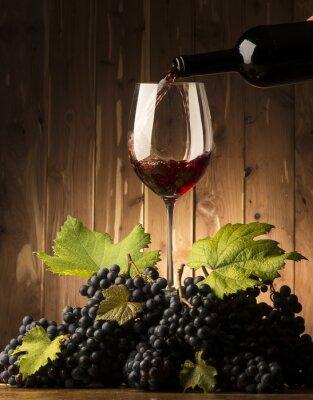 Carta da parati Vetro con vino rosso e grapeson il tavolo in legno