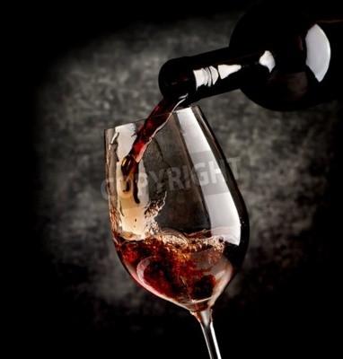 Carta da parati Vino che versa in bicchiere di vino su uno sfondo nero