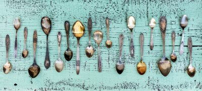 Carta da parati Vintage cutlery - spoons, forks and knives on an old wooden background.