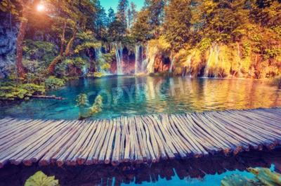 Carta da parati vista maestosa su acqua turchese e travi di sole nel parco nazionale dei laghi di Plitvice, Croazia
