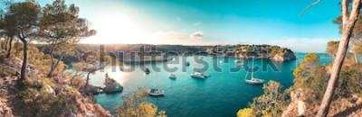 Carta da parati Vista panoramica di una baia sulla spiaggia con acqua blu turchese e barche a vela e yacht all'ancora con alberi di pino incorniciati. Bella romantica Cala Portals Vells, Mallorca, Spagna. Isole B