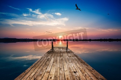 Carta da parati Vista prospettica di un pontile in legno sullo stagno al tramonto, con la riflessione perfettamente speculare