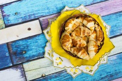 Carta da parati Самодельные круассаны в плетеной корзинке на желтой салфетке с цветочным узором на старом / вытертом полу