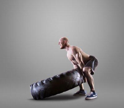 Poster Atletico giovane uomo di sollevamento di un pneumatico su sfondo grigio studio