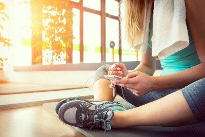 Poster Attraente donna bionda con il telefono astuto, riposa dopo l'allenamento in palestra