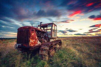 Poster Bel tramonto sul campo e vecchio trattore arrugginito