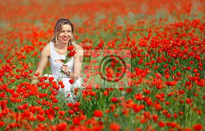 Poster Bella donna in campo di rosso brillante fiori di papavero in estate