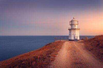 Poster Bella faro bianco sulla costa mare al tramonto. lan